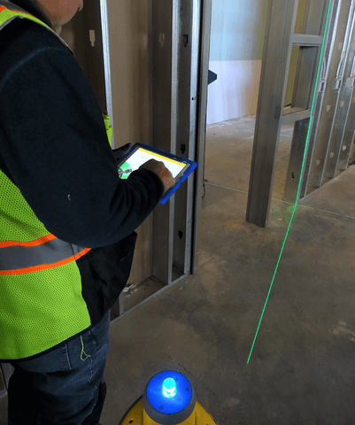 construction worker with laser layout system - Diversified Interiors
