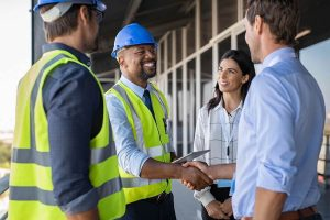 Smiling engineer in safety construction apparel shaking hands with a couple_business partner.